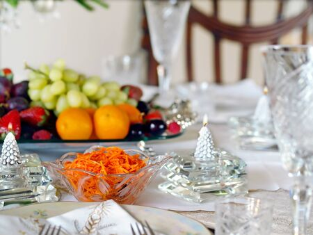 Holiday place setting with crystal dinnerware and candles photo