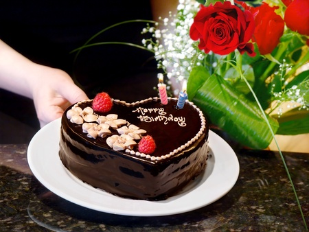 Female hands holding  chocolate heart cake and roses