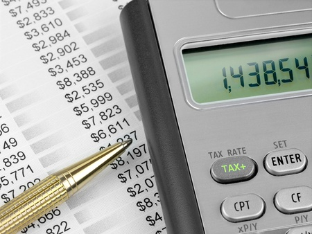 Pen and calculator with TAX button on the financial document photo