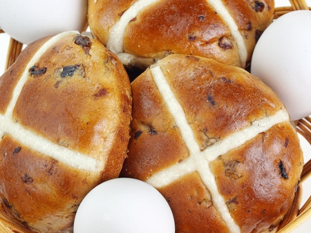 Closeup of basket with fresh hot cross buns and eggs Archivio Fotografico