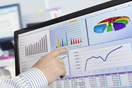 contabilidad: Hombre an�lisis de datos financieros y gr�ficos sobre la pantalla del ordenador