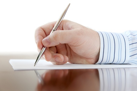 Closeup of a business man s hand with pen on the desk