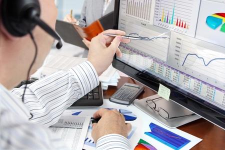 Man op een telefoon analyseren van financiële gegevens en grafieken op het computerscherm