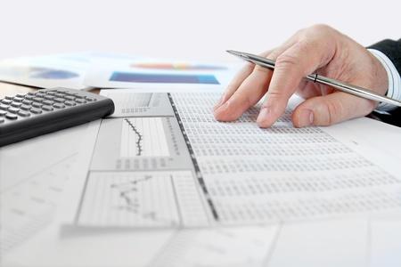 Male hand with pen analyzing  financial data  版權商用圖片