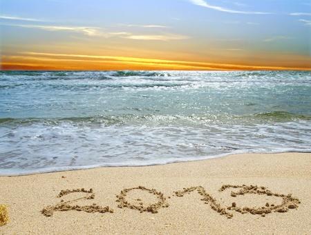 Numbers 2013 written in a sandy beach