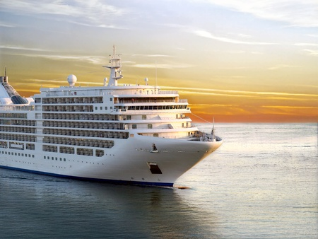 Luxury cruise ship sailing from port on sunset  Archivio Fotografico