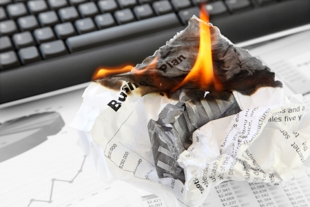 failed strategy: Burning Rejected Business Plan on the Office Background