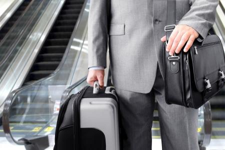 persona viajando: Hombre de negocios con su equipaje cerca de una escalera mec�nica en un aeropuerto