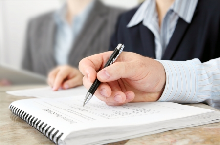 business training: Male Hand with Pen at the Meeting