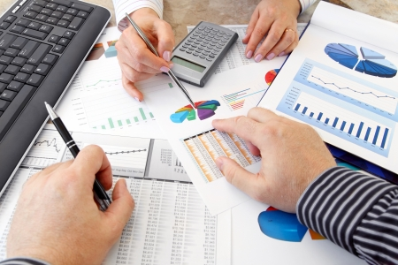 Hands with Financial  Charts  at Business Meeting in the Office photo