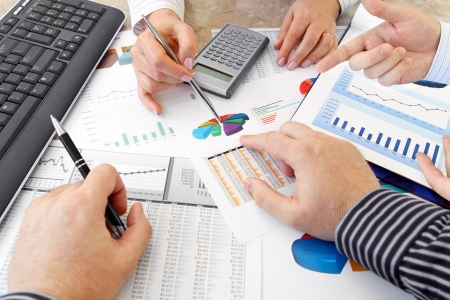 financial paperwork: Hands with Financial  Charts  at Business Meeting in the Office Stock Photo