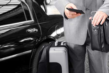 business travel: Traveling Businessman with His Luggage Using Phone