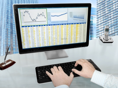Male Hands on the Keyboard in Front of Computer Screen with Financial Data and Charts