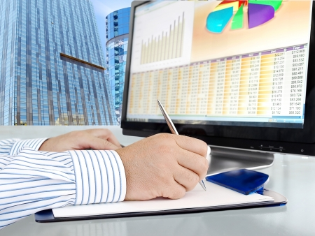 equities: Male Hand with Pen in Front of Computer Screen with Financial Data and Charts Stock Photo