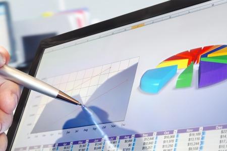 Man Analyzing Financial Data and Charts on Computer Screen 版權商用圖片