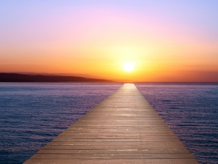 Wooden pier at sunset on the sea photo