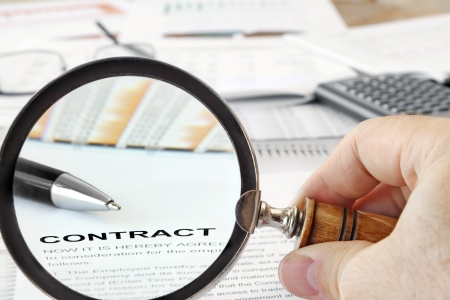 Magnifying Glass Over Contract Papers photo