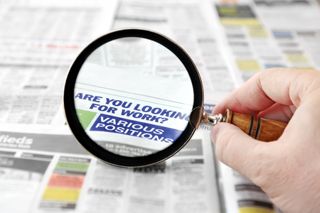 Magnifying glass over a newspaper job search section  版權商用圖片