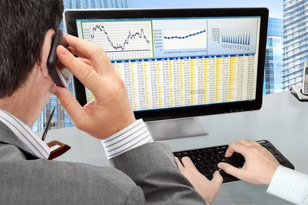 Analysing  Financial Data and Charts on Computer Screen  Stock Photo