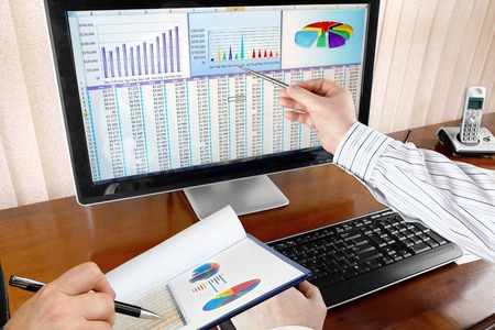 Businesspeople Analyzing Financial Data and Charts on Computer Screen in the Office 版權商用圖片