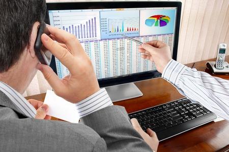 Analysing  Financial Data and Charts on Computer Screen  版權商用圖片