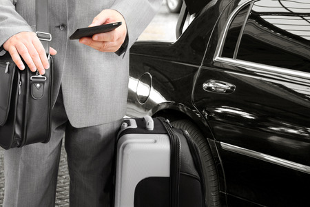 baggage: Traveling Businessman with His Luggage Using Phone Stock Photo