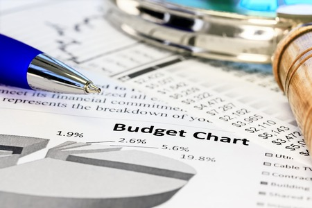 balanced budget: Pen with magnifying glass on the budget charts