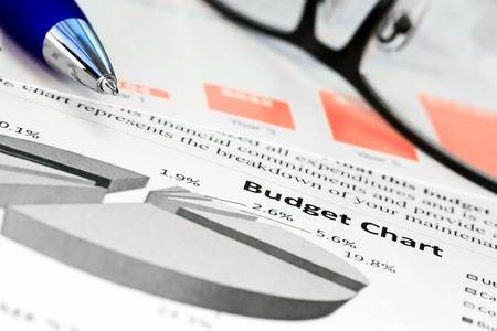 balanced budget: Pen with glasses on the  budget charts