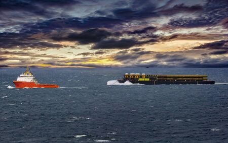 Tugboat towing  vessel with large pipes in the sea on stormy day