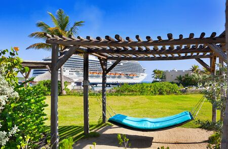 Hammock in relaxation area on tropical resort with cruise ship in background