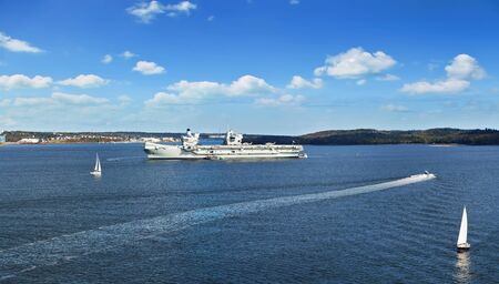 Panoramic view of Halifax Harbor with military ship and sail boats on sunny day