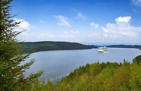 Panoramic view of the river Saguenay from Saguenay Fjord National park, Quebec, Canada with cruise ship in distance.