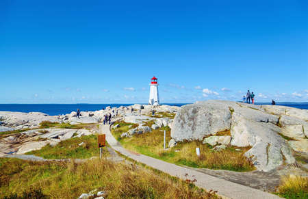 PEGGY'S COVE, NOVA SCOTIA, CANADA - SEPTEMBER 13, 2019: Panorama of Nova Scotia's iconic Peggys Cove Lighthouse on a sunny day. The lighthouse of Peggy's Cove a small rural community located on the eastern shore of St. Margarets Bay