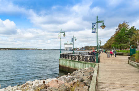 SYDNEY, NS, CANADA - SEPTEMBER 12, 2019: Sydney Waterfront Boardwalk with cruise ship Royal Caribbean Adventure of the Seas docked at port Sydney. The region is a popular Canadian cruise destination
