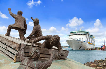 SYDNEY, NS, CANADA - SEPTEMBER 12, 2019: Merchant Mariner Monument with cruise ship Royal Caribbean Adventure of the Seas docked at port Sydney. The tourist region is a popular Canadian cruise destina