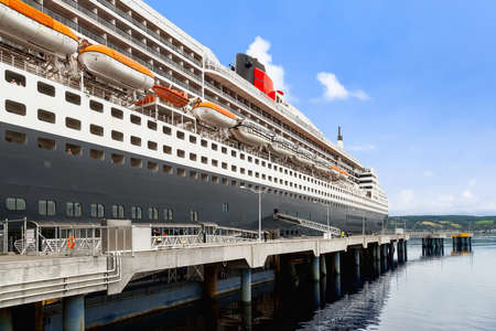 SAGUENAY, QC, CANADA - SEPTEMBER 10, 2019: RMS Queen Mary 2 ship docked at port. She is the largest ocean liner ever built, having served as the flagship of the Cunard Line