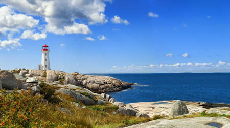 Panorama of harbor with Nova Scotia's iconic Peggys Cove Lighthouse on a sunny day