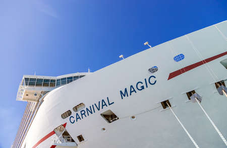 Grand Turk, Turks and Caicos Islands - MARCH 29, 2019: Side view of cruise ship Carnival Magic docked at port Grand Turk on the blue sky background