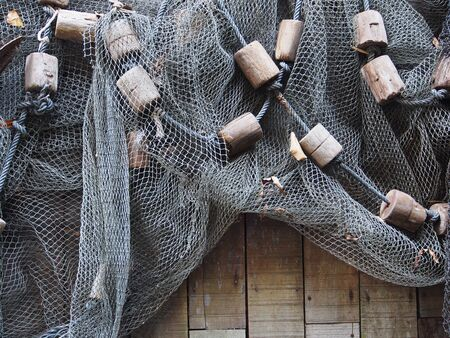 Fishing net is hanging on the wooden wall photo