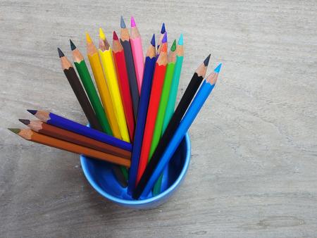school supplies color pencils shavings on wooden board photo
