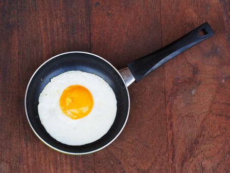 egg white: Fried eggs in a frying pan on wooden background