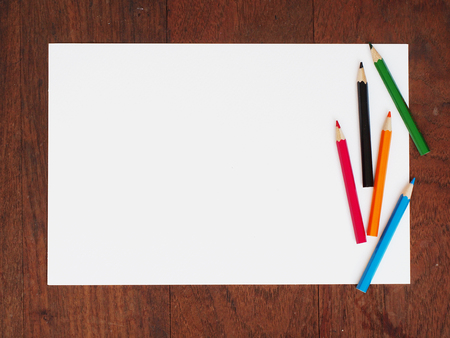 color pencil: Color pencils and a paper on wooden background