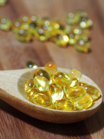 vitamin d: Fish oil capsules in a spoon