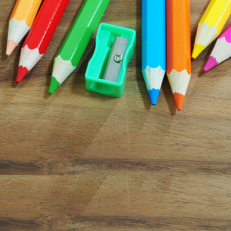 sacapuntas: Colored pencils and sharpener on wooden background