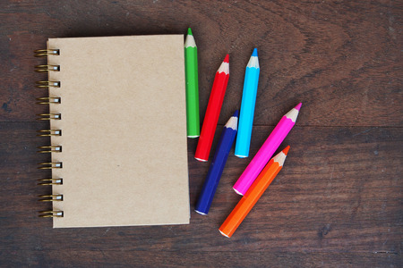 color pencils: Close note book and color pencil on wooden background