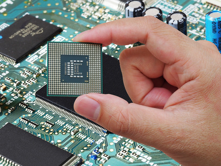 Central Processing Unit (CPU) in hand on printed green computer circuit board