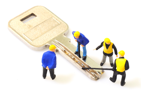 tool unlock: Group of locksmith workers are making the key isolated on white background