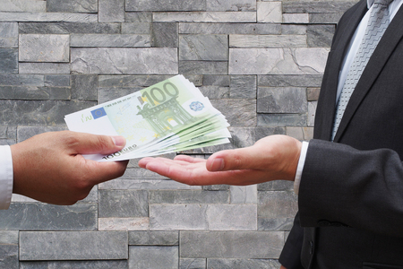 bribes: Businessman giving euro money to his business partner, Businessman offer a bribe to official, executive officer receive bribes from businessman isolated on white background, corruption concept Stock Photo
