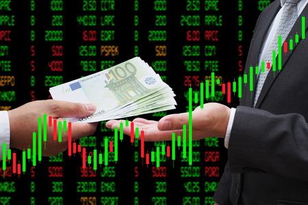 Belegger die euro geld geeft aan zijn zakenpartner, onder Kandelaargrafiek, investeringsconcept