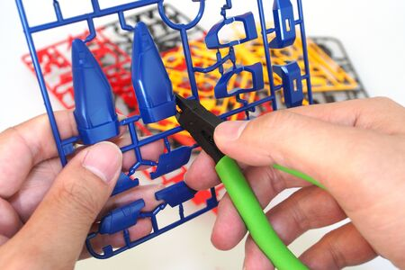 Man use nipper cutting a part of plastic model kit isolated on white background